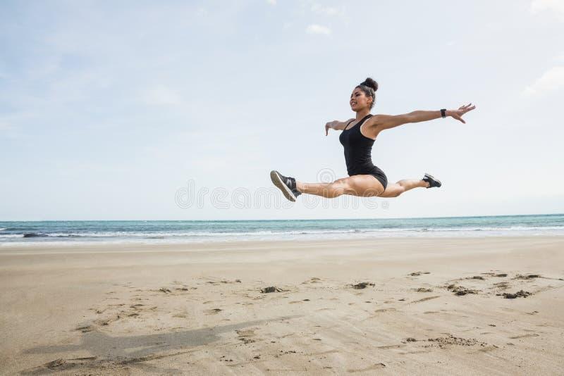 Geschikte vrouw die op het zand springen royalty-vrije stock afbeelding