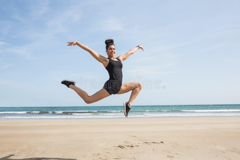 Geschikte vrouw die op het zand springen stock afbeelding