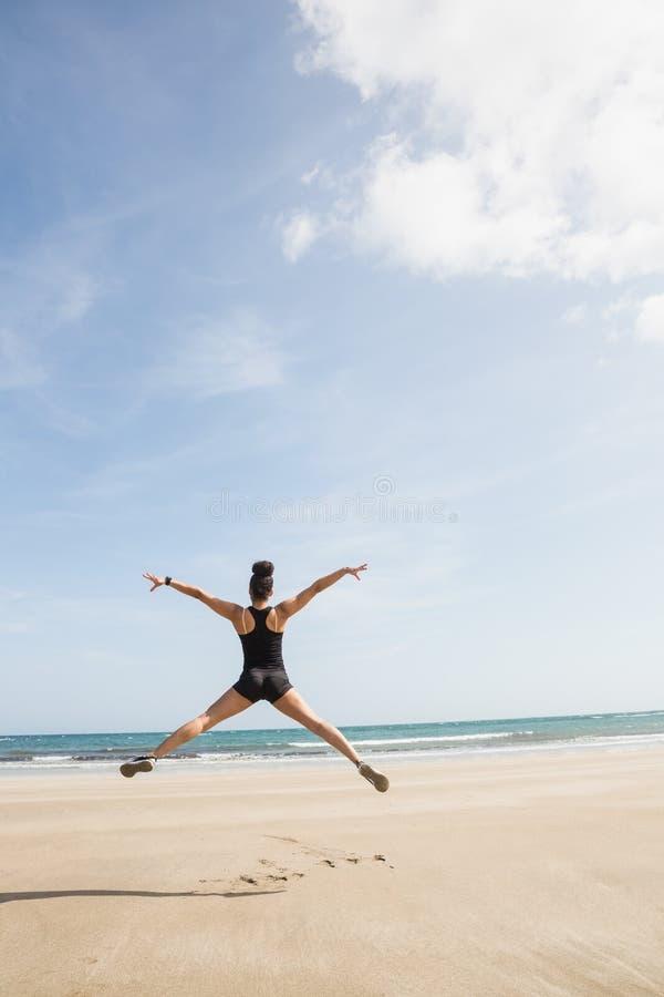 Geschikte vrouw die op het zand springen stock afbeeldingen