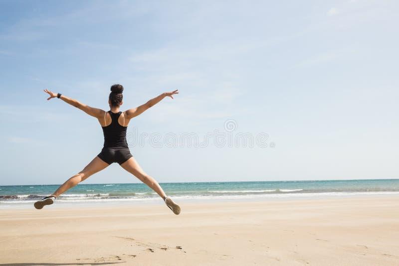 Geschikte vrouw die op het zand springen stock fotografie