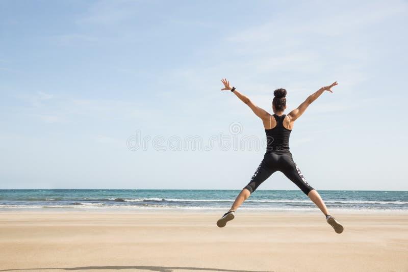 Geschikte vrouw die op het zand springen royalty-vrije stock foto's