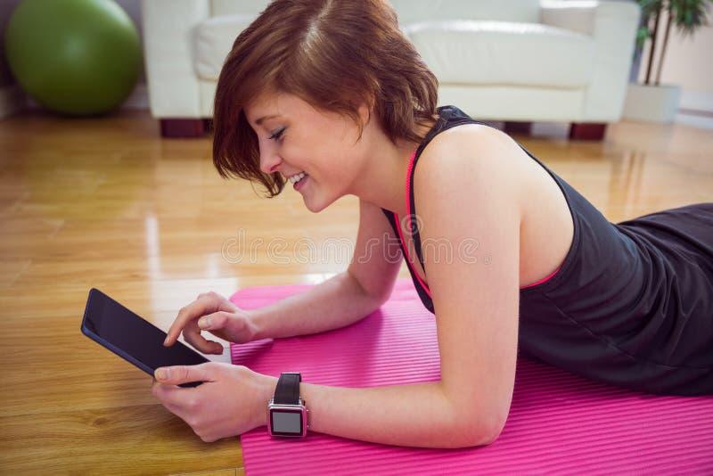 Geschikte vrouw die tabletpc op mat met behulp van royalty-vrije stock afbeelding