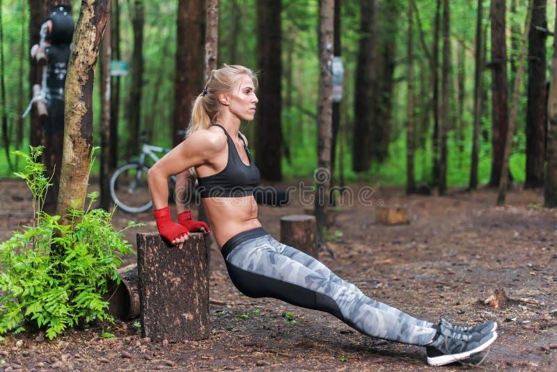 Geschikte vrouw die tricepsonderdompelingen doen bij park Geschiktheidsmeisje die in openlucht met eigen lichaamsgewicht uitoefen stock foto