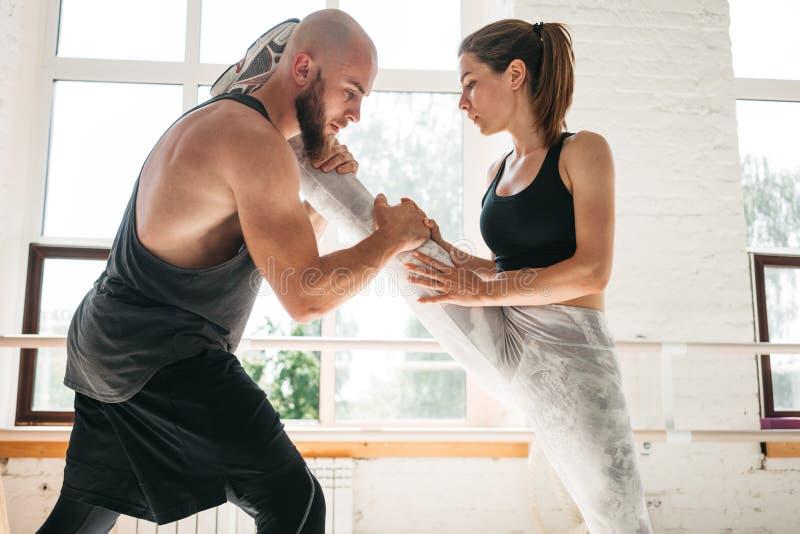 Geschikte vrouw die uitoefenend zich het uitrekken bij de gymnastiek met mannelijke trainer doen royalty-vrije stock fotografie