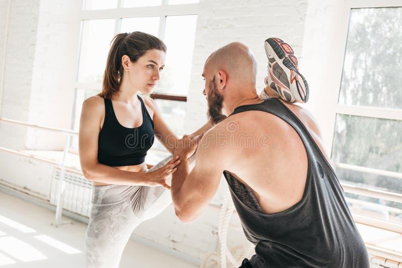 Geschikte vrouw die uitoefenend zich het uitrekken bij de gymnastiek met mannelijke trainer doen stock afbeelding