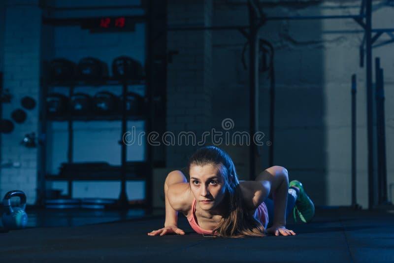 Geschikte vrouw in kleurrijke sportkleding die burpees op een oefeningsmat doen in een grungy industriële typeruimte stock foto's