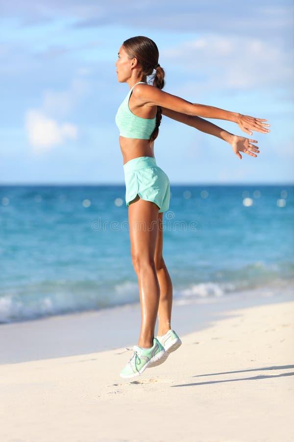 Geschikte vrouw opleidingsbenen met springende de hurkzitoefeningen van de hiittraining op strand royalty-vrije stock foto