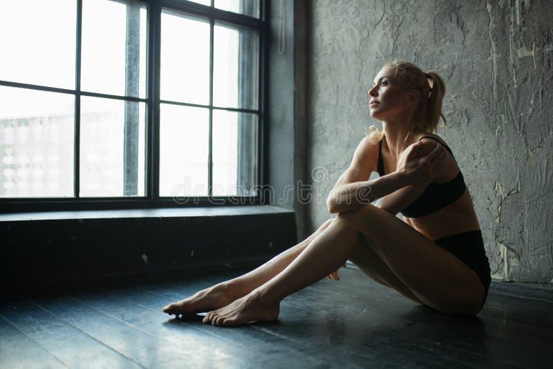 Geschikte vrouw in profielzitting op vloer in zoldergymnastiek stock foto