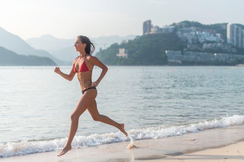 Geschikte vrouwelijke atleet die bikini dragen die op strand met zon die in camera en de heuvels van de hoteltoevlucht op achterg stock foto's