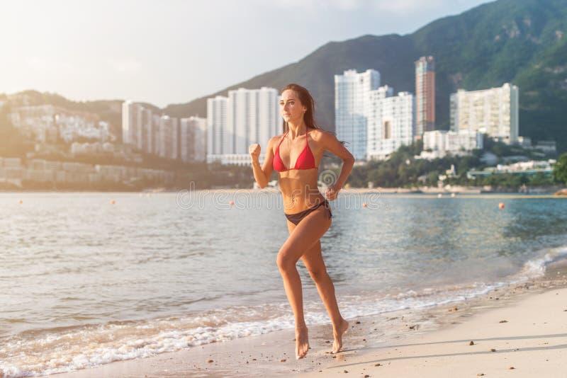 Geschikte vrouwelijke atleet die bikini dragen die op strand met zon die in camera en de heuvels van de hoteltoevlucht op achterg royalty-vrije stock foto