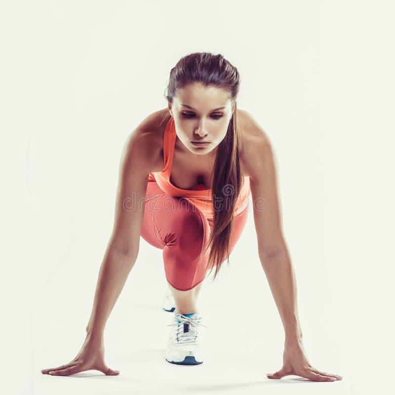 Geschikte vrouwelijke atleet klaar om over grijze achtergrond te lopen Het vrouwelijke geschiktheid model voorbereidingen treffen royalty-vrije stock foto