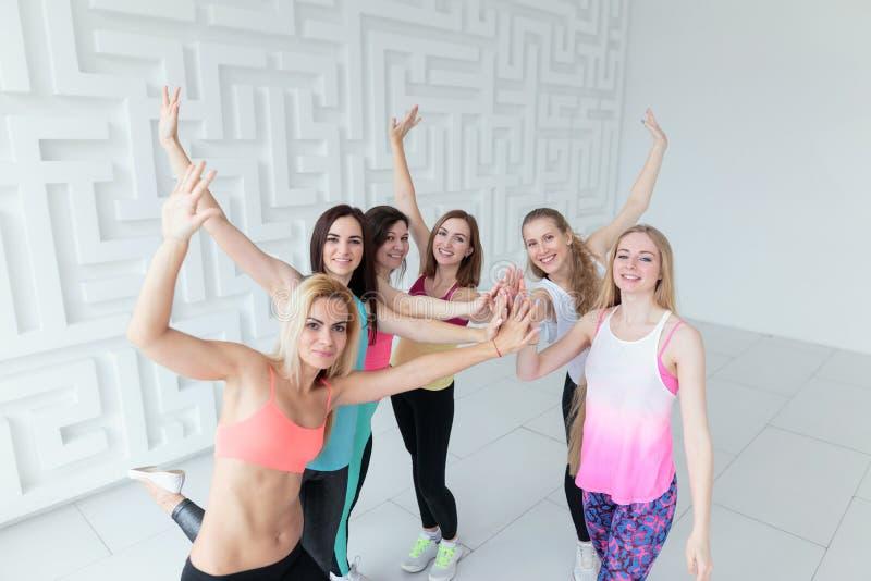 Geschikte vrouwen die sportkledings toetredende handen samen dragen het bekijken camera stock afbeelding