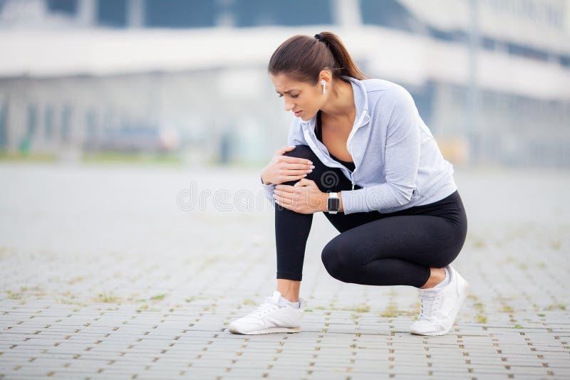 Geschiktheid Atletische vrouwen die knie houden die een trauma hebben stock fotografie