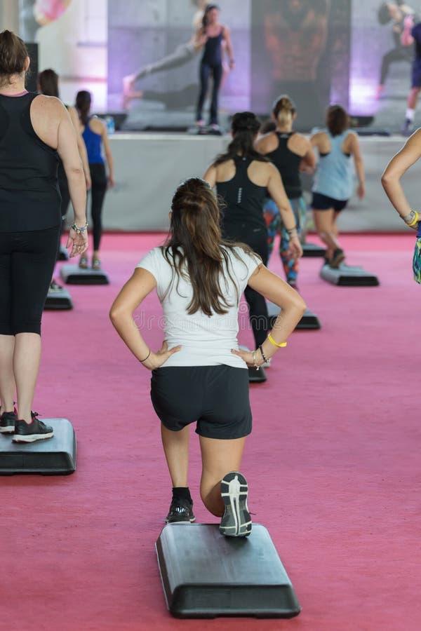 Geschiktheid bij gym: Mensen die oefeningen doen in klasse met Step Platform, Muziek en Leerkrachten op Stadium stock fotografie