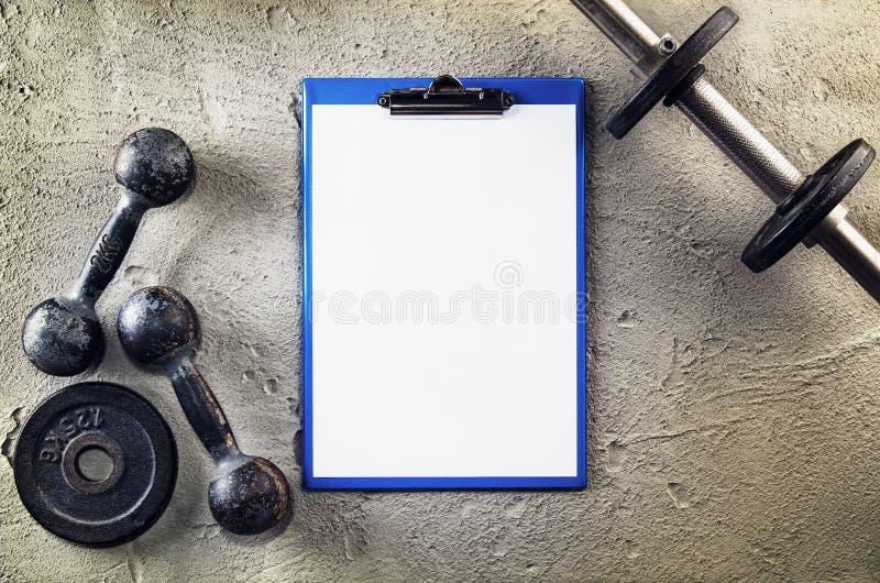 Geschiktheid of bodybuilding achtergrond Oude ijzerdomoren op conretevloer in de gymnastiek Foto hierboven wordt genomen die van, royalty-vrije stock afbeeldingen