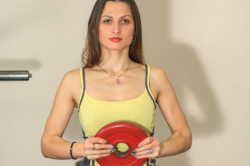 Geschiktheid en fysieke oefeningen Het jonge mooie witte meisje in een geel en grijs sportenkostuum leidt met een spruit van de b royalty-vrije stock foto
