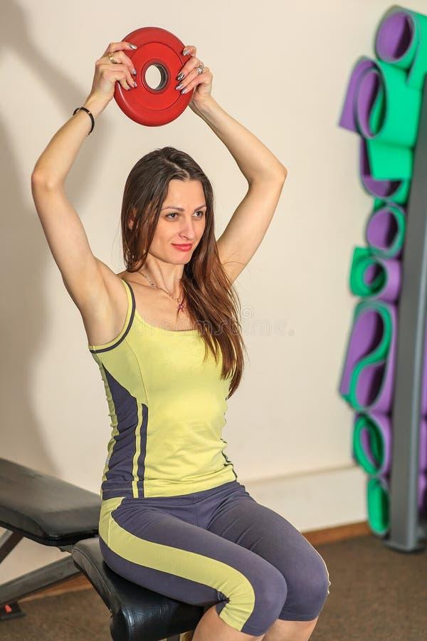 Geschiktheid en fysieke oefeningen Het jonge mooie witte meisje in een geel en grijs sportenkostuum leidt met een spruit van de b stock fotografie