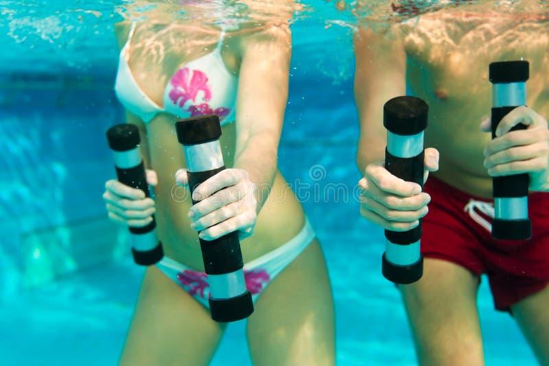 Geschiktheid - gymnastiek onder water in zwembad stock foto