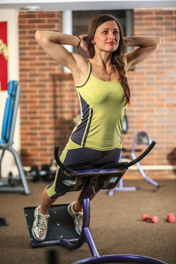 Geschiktheid Het jonge mooie witte meisje in een geel en grijs sportenkostuum doet oefeningen op opleidingsapparaten in de fitnes royalty-vrije stock afbeelding