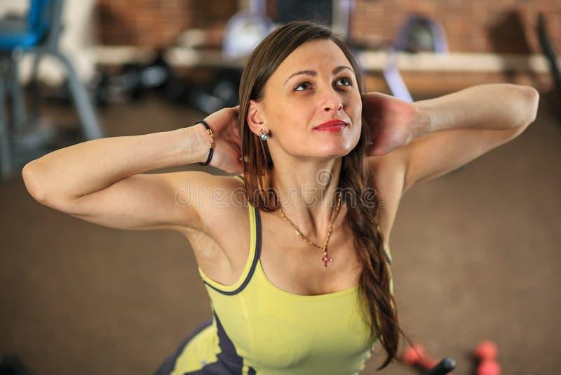 Geschiktheid Het jonge mooie witte meisje in een geel en grijs sportenkostuum doet oefeningen op opleidingsapparaten in de fitnes royalty-vrije stock fotografie