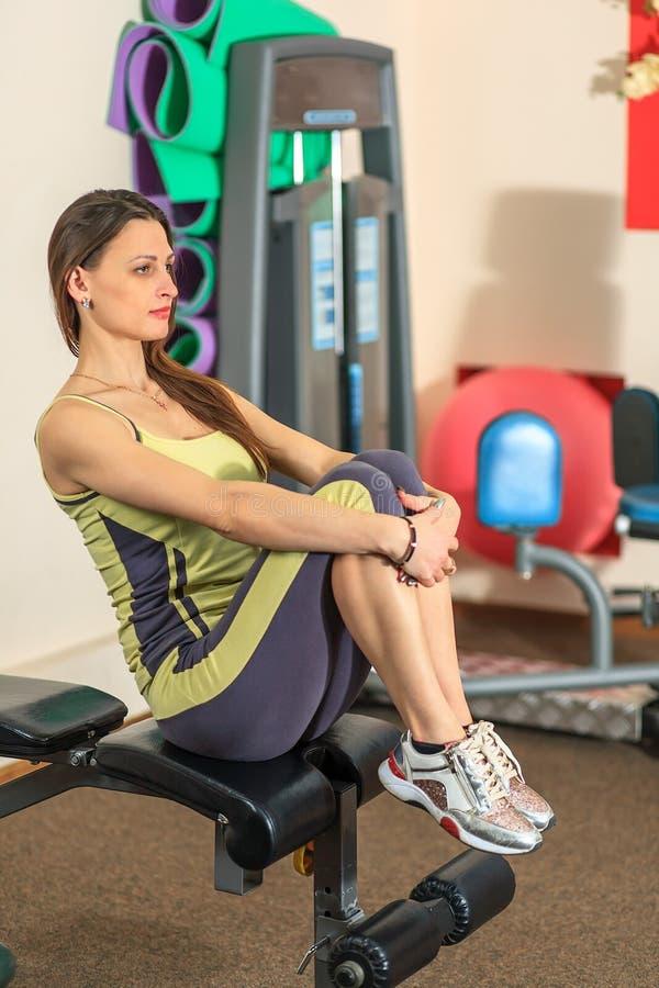 Geschiktheid Het jonge mooie witte meisje in een geel en grijs sportenkostuum doet oefeningen op opleidingsapparaten in de fitnes royalty-vrije stock foto