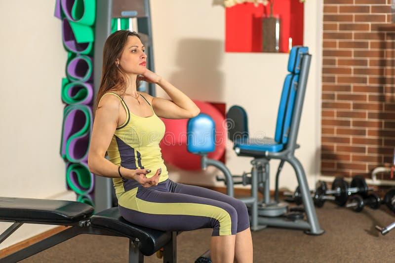 Geschiktheid Het jonge mooie witte meisje in een geel en grijs sportenkostuum doet oefeningen op opleidingsapparaten in de fitnes stock foto's