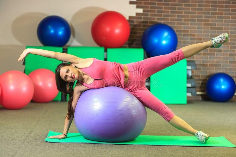 Geschiktheid Het jonge mooie witte meisje in een roze sportenkostuum doet lichaamsbewegingen met een violette geschikte bal op he royalty-vrije stock afbeelding
