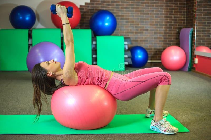 Geschiktheid Het jonge mooie witte meisje in roze sportenkostuum doet lichaamsbewegingen met dumbells en geschikte bal op het fit stock afbeeldingen
