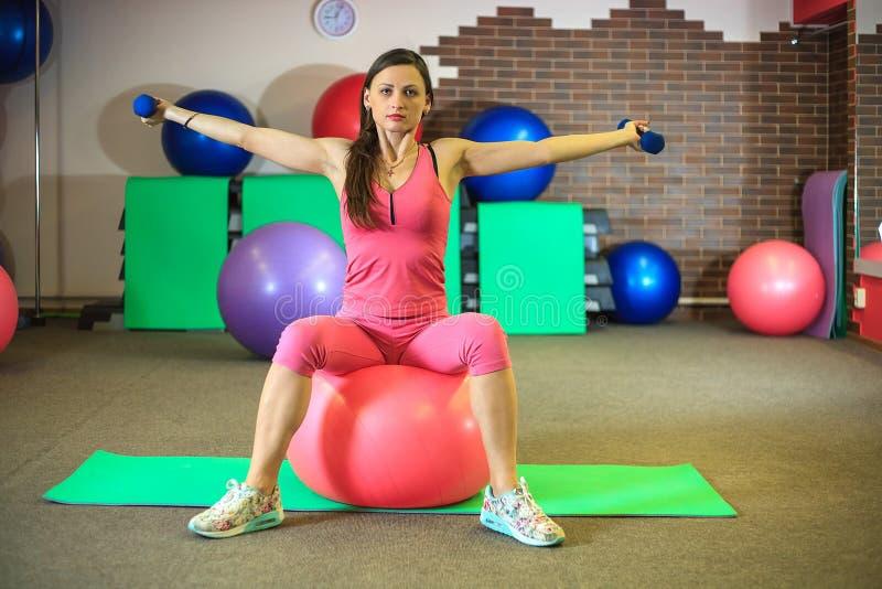 Geschiktheid Het jonge mooie witte meisje in roze sportenkostuum doet lichaamsbewegingen met dumbells en geschikte bal op het fit stock fotografie
