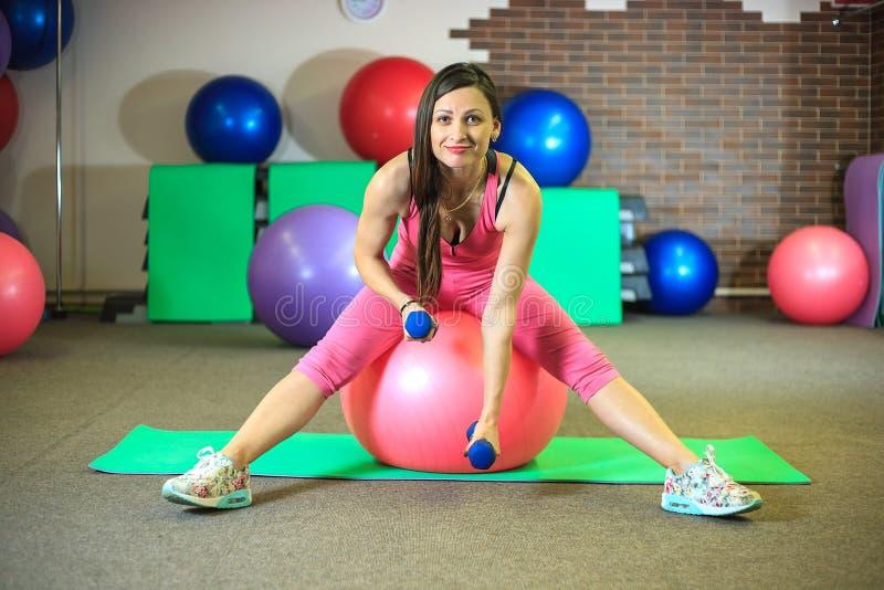 Geschiktheid Het jonge mooie witte meisje in roze sportenkostuum doet lichaamsbewegingen met dumbells en geschikte bal op het fit stock afbeelding