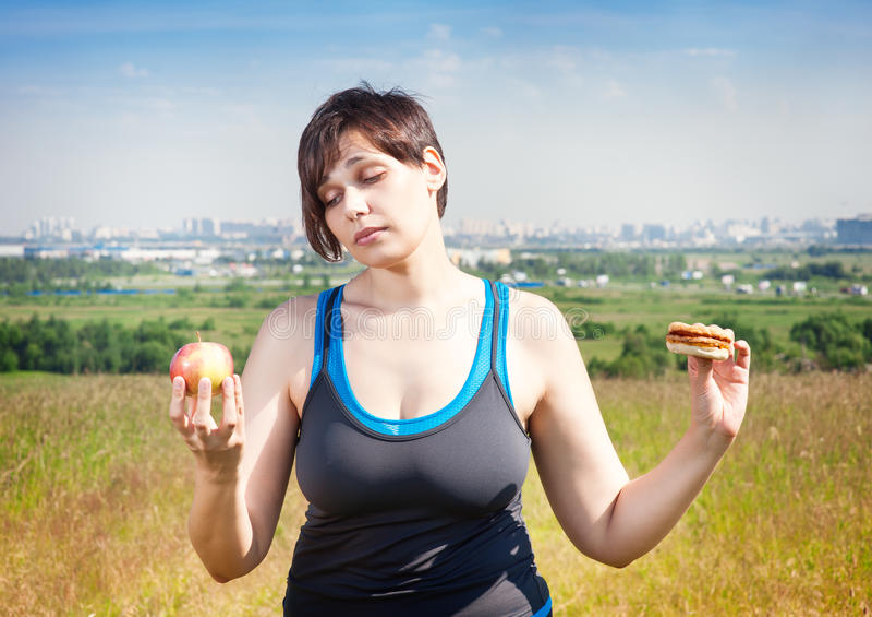 Geschiktheid plus groottevrouw die keus tussen gezond en troep F maken stock foto