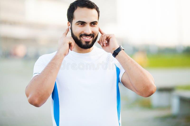 Geschiktheid Sportmens die die hoofdtelefoons voor het luisteren muziek op ochtend met behulp van in park in werking wordt gestel stock afbeelding