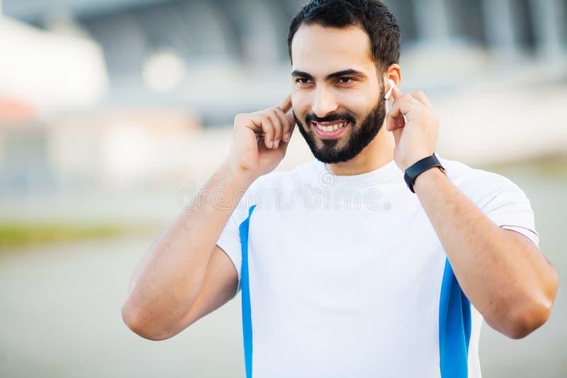 Geschiktheid Sportmens die die hoofdtelefoons voor het luisteren muziek op ochtend met behulp van in park in werking wordt gestel royalty-vrije stock foto's
