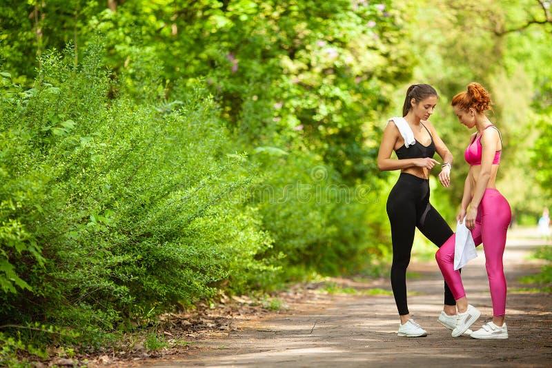Geschiktheid Twee vrouwelijke agenten die benen in openlucht in park in de zomer uitrekken stock foto's