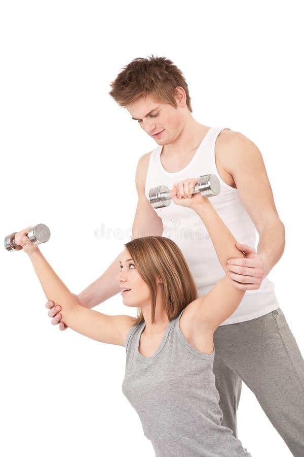 Geschiktheid - Vrouw met instructeur het opheffen gewichten stock foto