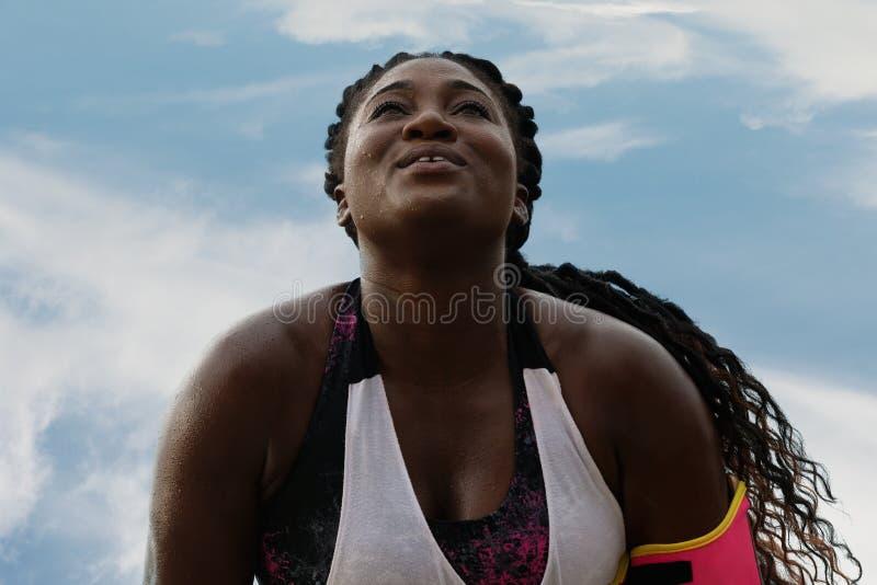 Geschiktheids Afrikaanse vrouw die opdrukoefeningen dicht omhoog doen onder regen stock foto's