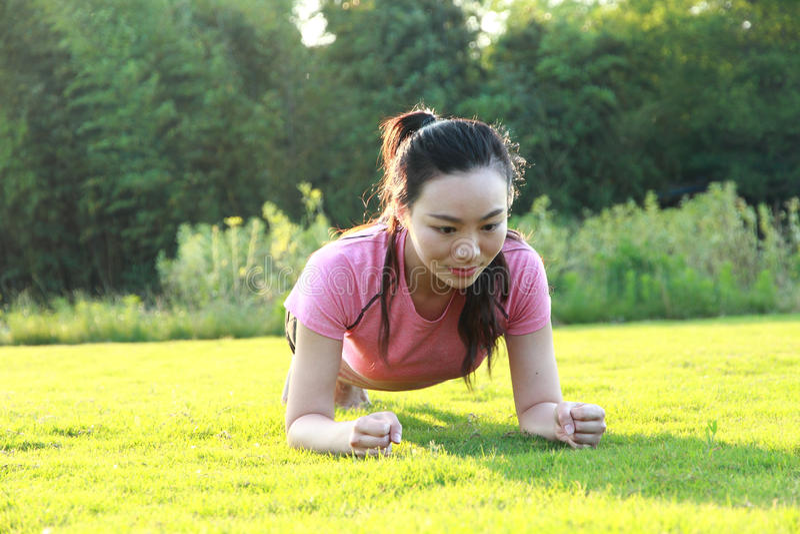 Geschiktheids Aziatische Chinese woman do plank oefening stock foto