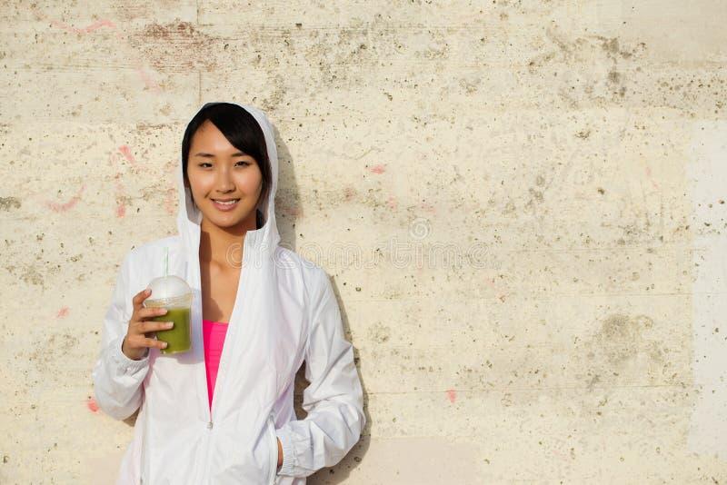 Geschiktheids Aziatische vrouw die een rust voor het drinken nemen detox smoothie royalty-vrije stock afbeeldingen