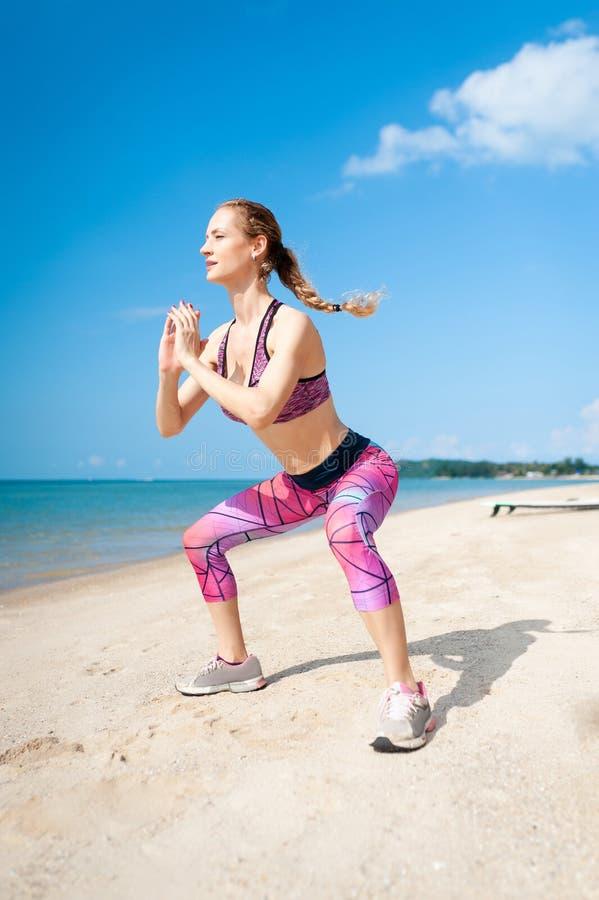 Geschiktheids het jonge vrouw boort uitwerken en glutes met lichaamsgewichttraining doend uit hurkende oefeningen op strand stock fotografie