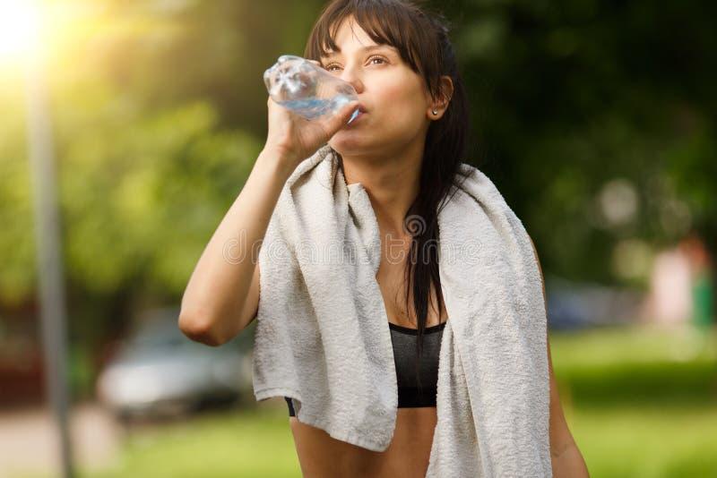 Geschiktheids het jonge vrouw rusten en drinkwater na opleiding stock foto's