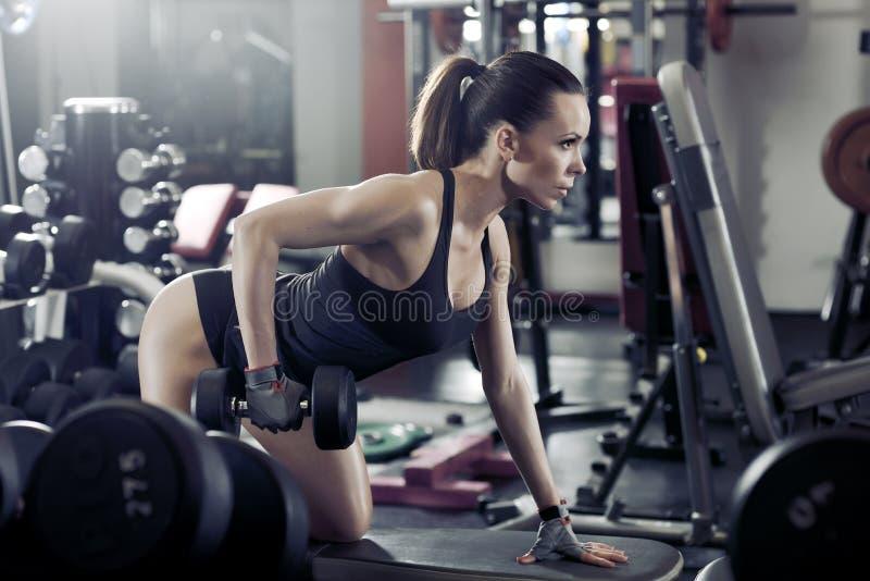 Geschiktheids jong sexy meisje in de gymnastiek die oefeningen met domoor doen stock afbeelding