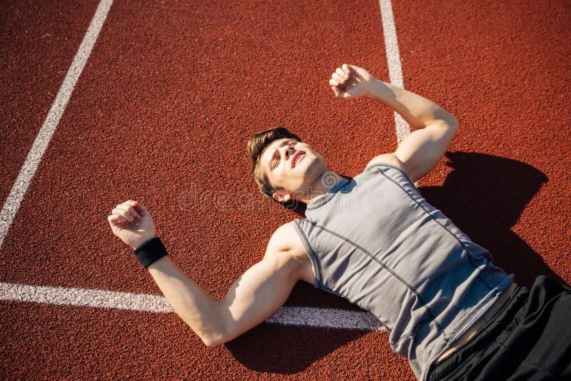 Geschiktheids jonge mens die op renbaan na harde training leggen stock foto