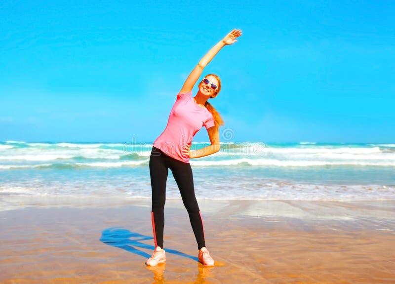 Geschiktheids jonge vrouw die uitrekkende oefening op het strand doen royalty-vrije stock afbeeldingen