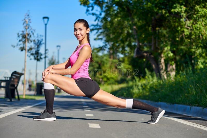 Geschiktheids jonge vrouw het uitrekken zich benen na looppas in openlucht sportportret stock afbeeldingen