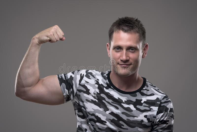 Geschiktheids mannelijk model in de verbuiging van het legeroverhemd wapen en het tonen van bicep spieren stock foto's