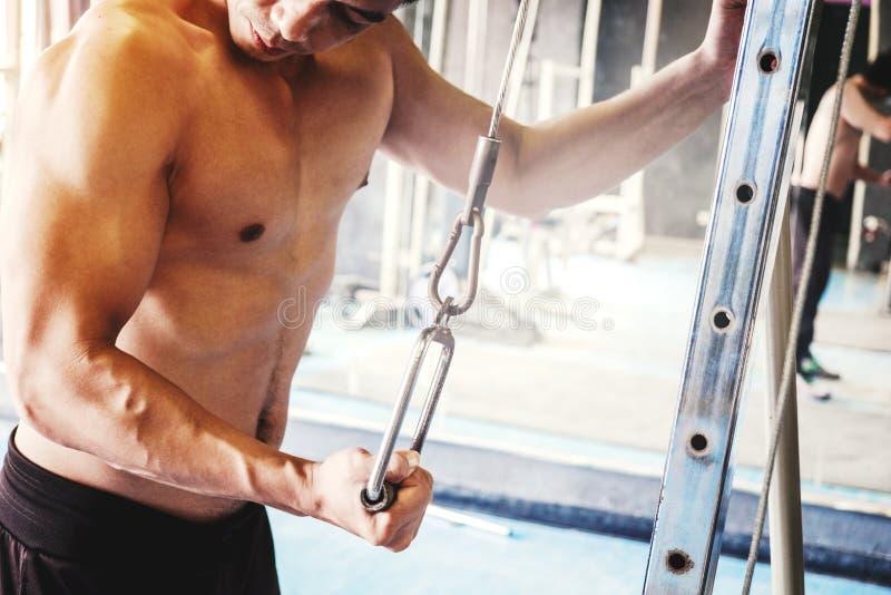 Geschiktheids Sterke Mens die Zwaargewicht Oefening op Machine in gymnastiek doen stock foto's