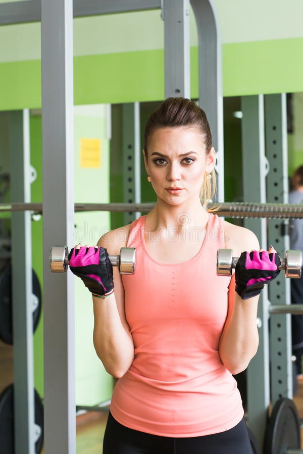 Geschiktheids vrouwelijke vrouw die haar training met domoren in gymnastiek doen stock foto's