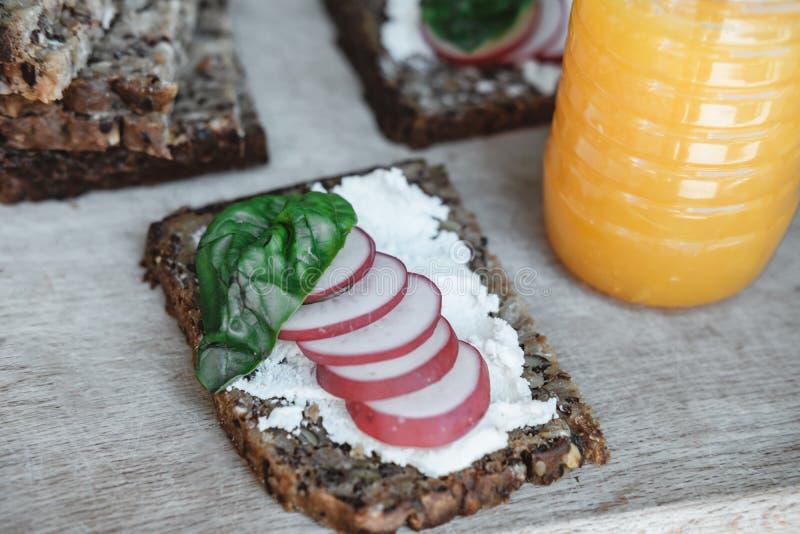 Geschiktheidsbrood met kwark, radijs en basilicum en Oranje j stock foto