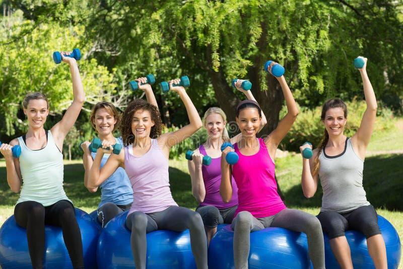 Geschiktheidsgroep die oefeningsballen in park gebruiken royalty-vrije stock afbeelding