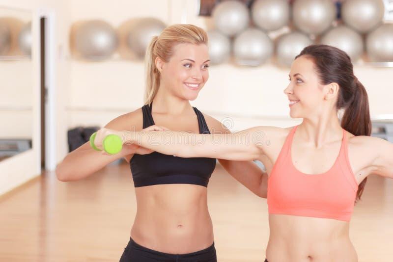 Geschiktheidsinstructeur die vrouw in gymnastiek helpen royalty-vrije stock afbeelding